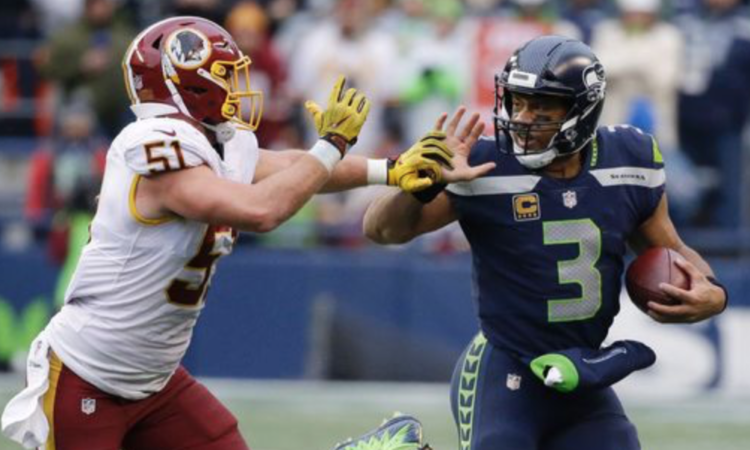 Seattle Seahawks quarterback Russell Wilson being chased by Redskin Will Compton (AP Photo/Elaine Thompson)